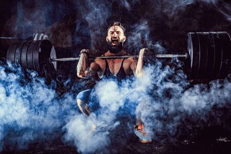 Photo pour Muscular bearded tattoed fitness man doing deadlift a barbell over his head in modern fitness center. Functional training. Snatch exercise - image libre de droit