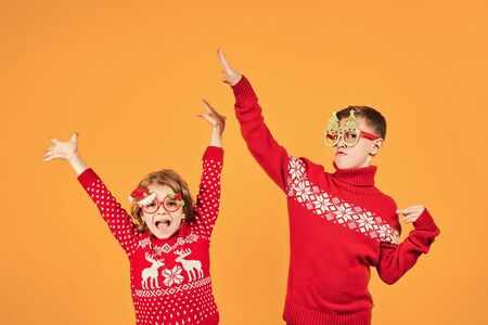 Photo pour Confident children in warm red Christmas sweaters and decorated glasses looking at camera on yellow background - image libre de droit