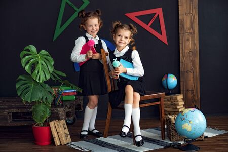 Photo for Little twins in school uniform holding books while studying together - Royalty Free Image