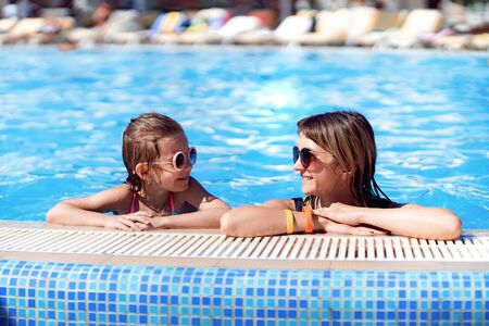 Photo pour Happy family, young active mother and adorable little daughter having fun in a swimming pool enjoying summer vacation at a tropical resort. - image libre de droit