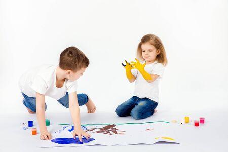 Photo pour Two pretty child friends boy and girl in white shirts and blue jeans, trendy hair style, barefoot, drawing pictures on white sheet of paper by paints isolated on white. Studio shot. - image libre de droit