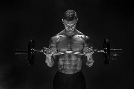 Photo pour Studio portrait of topless bodybuilder performing biceps exercise with concentrated face over black background with smoke. Cutout. Very brawny guy bodybuilder. - image libre de droit
