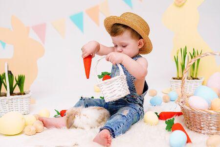 Foto de Happy little boy in hat feeds cute fluffy Bunny. Friendship with Easter Bunny. Spring photo with little boy with his Bunny. boy is holding a cute little rabbit. - Imagen libre de derechos