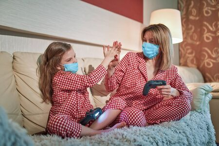 Photo pour Woman and young girl wearing pajamas and medical protective masks sitting on sofa in living room with video game controllers at home isolation auto quarantine, covid-19. - image libre de droit