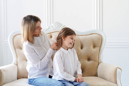 Photo for Mom straightens her daughters hair. Parents and children. Family values and relationships of aunts and parents. - Royalty Free Image
