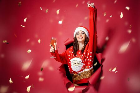 Attractive brunette woman in Christmas hat and pullover with Santa design coming out of torn red background with glass of champagne under confetti