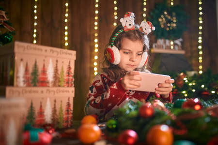 Photo pour Girl using phone near Christmas tree in the decorative interior. Christmas and New Year photo. - image libre de droit