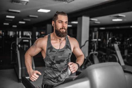 Foto de Adult strong bearded man running on treadmill in gym. - Imagen libre de derechos