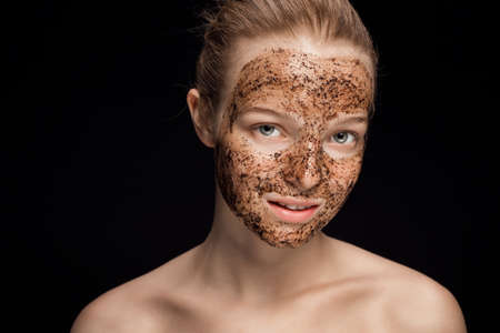 Photo pour Skin scrub Coffee grounds mask on the face of a beautiful young woman - image libre de droit