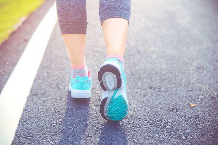Foto für Close up on shoe, Runner athlete feet running on road under sunlight in the morning. - Lizenzfreies Bild