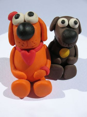 A plasticine toys. Handmade. The little funny dogs on the white background.