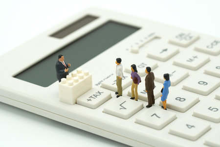 Foto de Miniature people Pay queue Annual income (TAX) for the year on calculator. using as background business concept and finance concept with copy space  for your text or  design. - Imagen libre de derechos
