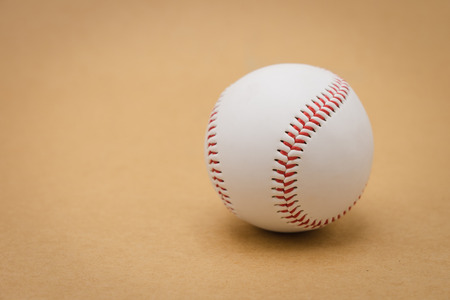 Isolated baseball on a brown background and red stitching baseball. White baseball with red thread.Baseball is a national sport of Japan. It is popular.