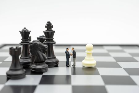 Photo pour Miniature 2 people businessmen Shake hands standing on a chessboard with a chess piece on the back Negotiating in business. as background business concept and strategy concept with copy space. - image libre de droit