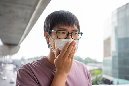 HandsomeMan wearing face mask protect filter against air pollution (PM2.5) or wear N95 mask. protect pollution, anti smog and viruses, Air pollution caused health problem. Global warming concept.の素材 [FY310139380561]