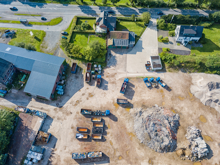 Aerial view of a recycling yard with trucks and containers.