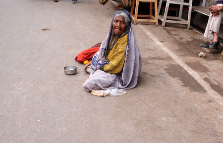 Photo for Unidentified old indian beggar waits for alms on a street on the ghat along the sacred Sarovar lake in Pushkar, India on February 18, 2016. - Royalty Free Image