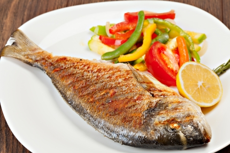 Foto de Grilled dorado fish with lemon and vegetables  - Imagen libre de derechos