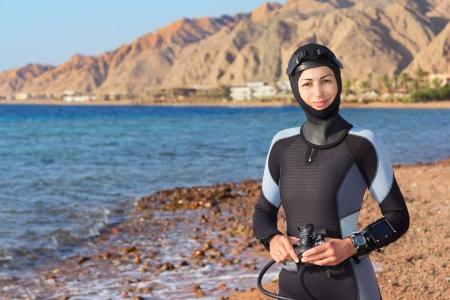 Photo pour Woman diver prepares to dive - image libre de droit