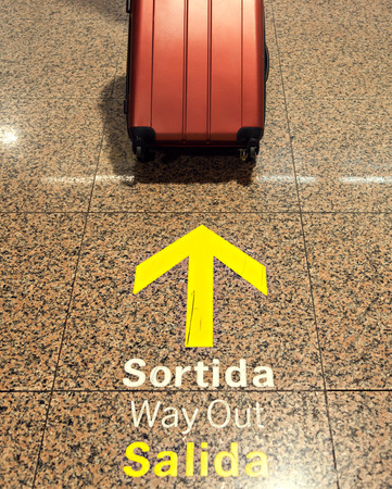 The suitcase is next to the exit signs in English, Spanish and Catalan languages