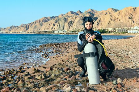Photo pour Female diver checking her equipment on the coast before diving. Egypt, Dahab, Red Sea. Looking At Camera. - image libre de droit