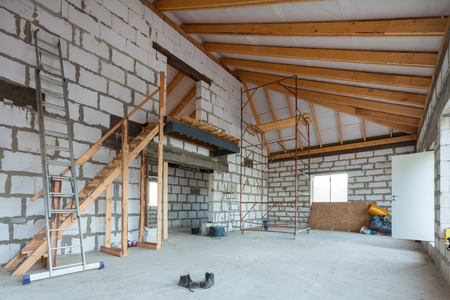 Photo pour Ladder, parts of scaffolding and construction material on the floor during on the remodeling, renovation, extension, restoration, reconstruction and construction - image libre de droit