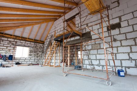Foto de Ladder, parts of scaffolding and construction material on the floor during on the remodeling, renovation, extension, restoration, reconstruction and construction - Imagen libre de derechos