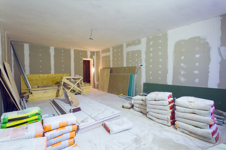 Foto de Materials for constraction (putty packs, sheets of plasterboard or drywall)  in apartment is under construction, remodeling, renovation, extension, restoration and reconstruction. - Imagen libre de derechos
