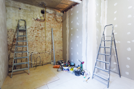 Interior of room during of install of plasterboard for making gypsum walls on the brick wall in an apartment is under construction, remodeling, renovation,  restoration, reconstruction