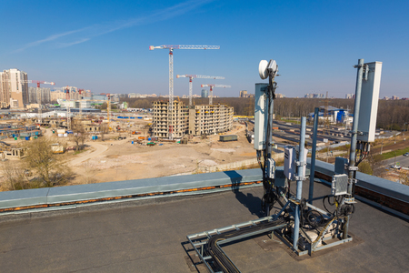 Photo pour Panel antennas of GSM DCS UMTS LTE bands and radio unit are as part of communication equipment of basic station are installed on the roof that is located near construction site. - image libre de droit
