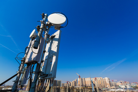Photo for Panel antenna of GSM DCS UMTS LTE bands and radio unit are as part of communication equipment of basic station are installed on the roof and sky and city are as background - Royalty Free Image