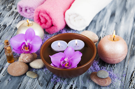 Spa composition with spa accessories, orchid flowers and towels on a wooden background