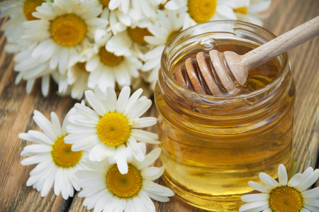 Fresh spring honey with chamomile flowers on wooden table