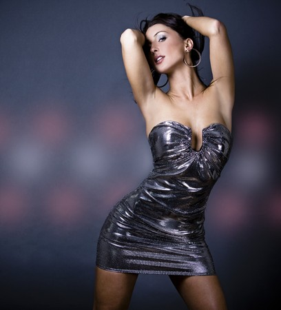 pretty brunette woman wearing dress on dark background