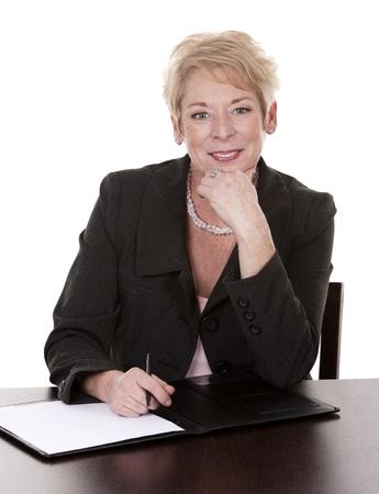 Foto für mature woman sitting behind desk and writing notes down - Lizenzfreies Bild