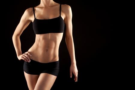 Photo pour female fitness model posing on black background - image libre de droit