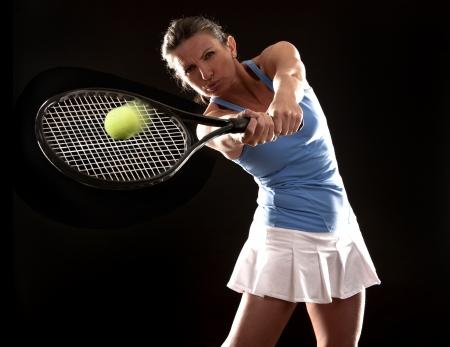 Photo pour brunette playing tennis on black background - image libre de droit