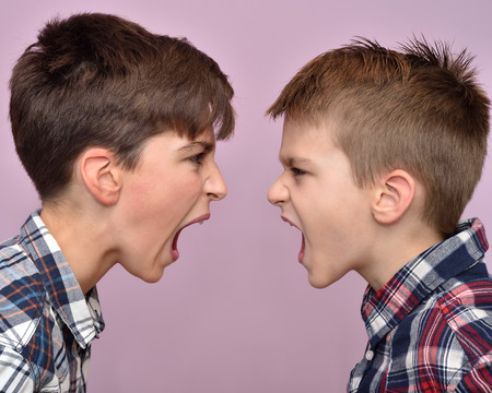Photo pour Two angry brothers standing face to face, quarreling, shouting and looking at each other - image libre de droit