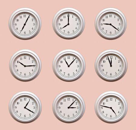 Foto de A lot of same clocks showing different times hanging on the pale orange wall - Imagen libre de derechos