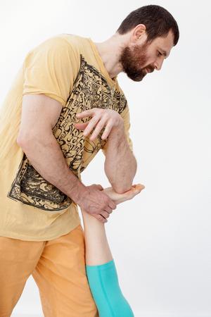 Massage and rehabilitation. Man manipulates on woman\'s leg.