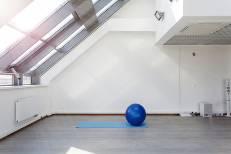 Gym for fitness exercises. Fitbol and mat  lie on the floor. The room is flooded with sunlight from the window, the glare on the white wall. Audio system with speakers in the background.