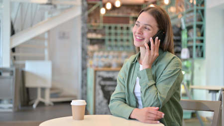 Photo pour Cheerful Young Woman Talking on Phone in Cafe - image libre de droit