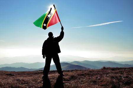 Successful silhouette man winner waving Saint Kitts and Nevis flag on top of the mountain peak