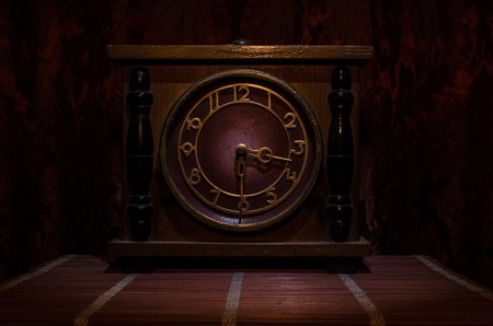 Time concept - vintage wood clock face with grunge texture at dark red maroon curtain background,
