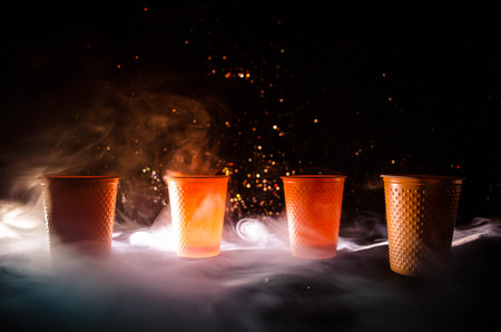 Stack of orange plastic cups with straw on dark background with smoke