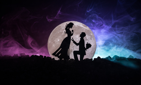 Foto de Amazing love scene. Silhouettes of man making proposal to woman or Silhouettes of couple against big moon at background. Selective focus - Imagen libre de derechos