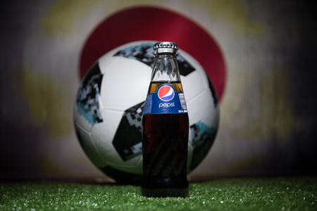 BAKU,AZERBAIJAN - JULY 01, 2018 : Creative concept. Official Russia 2018 World Cup football ball The Adidas Telstar 18 and Pepsi Classic in a glass bottle on grass. Support your country concept