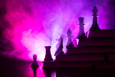 Photo pour Business hierarchy. Strategy concept with chess pieces. Chess standing on a pyramid of books with the king at the top. Dark foggy background with toned light. Copy space. - image libre de droit