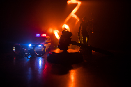 Photo pour Law theme, mallet of the judge on wooden desk with Lady Justice Statue. Silhouette of handcuffs with police car on backside. Law gavel on dark foggy background with light. - image libre de droit