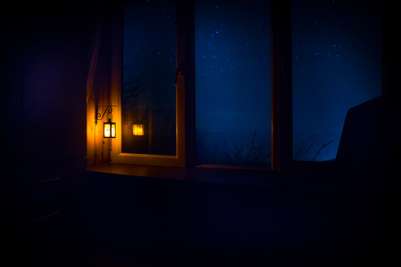 Photo pour Night scene of stars seen through the window from dark room. Night sky inside dark room viewing from window with old vintage lantern. Long exposure shot - image libre de droit